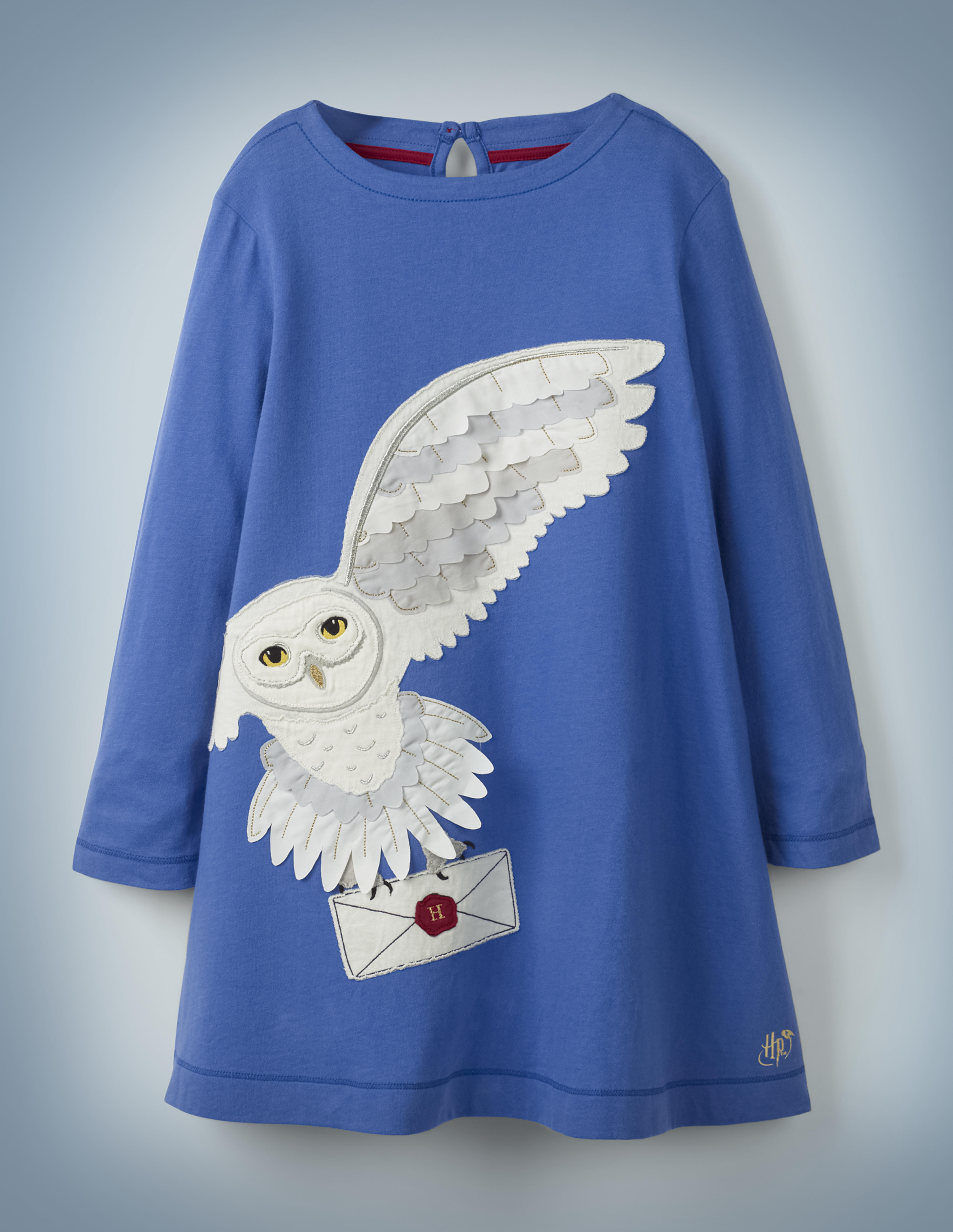 The Mini Boden Hedwig Post Dress in blue features a large, off-center image of Harry Potter's beloved owl carrying a Hogwarts acceptance letter in her talons. It retails between £28 and £32.