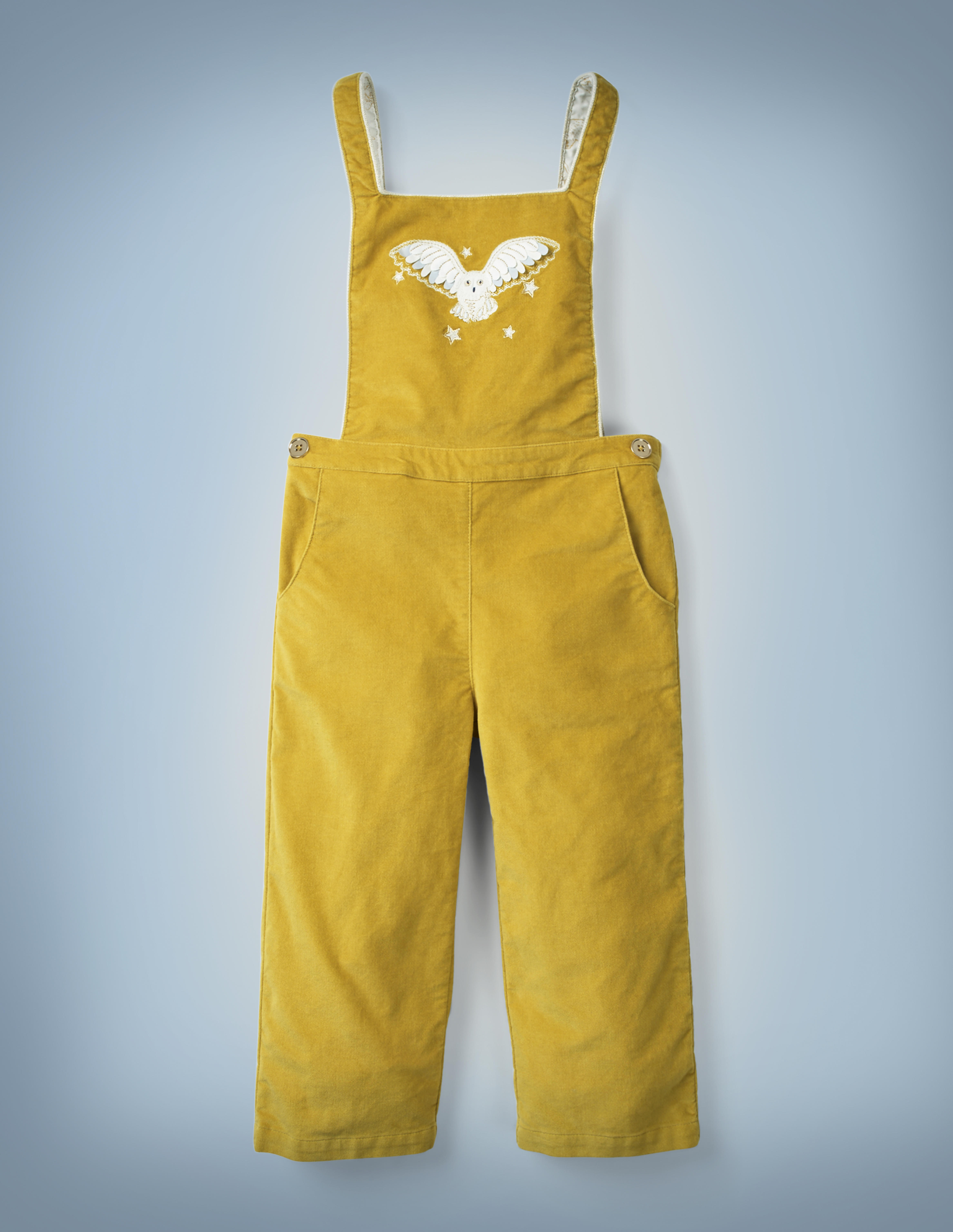 The Mini Boden Hedwig Dungarees in mustard yellow feature a design of Harry Potter's beloved owl flying through the stars on the breast of the overalls. They retail at £40.