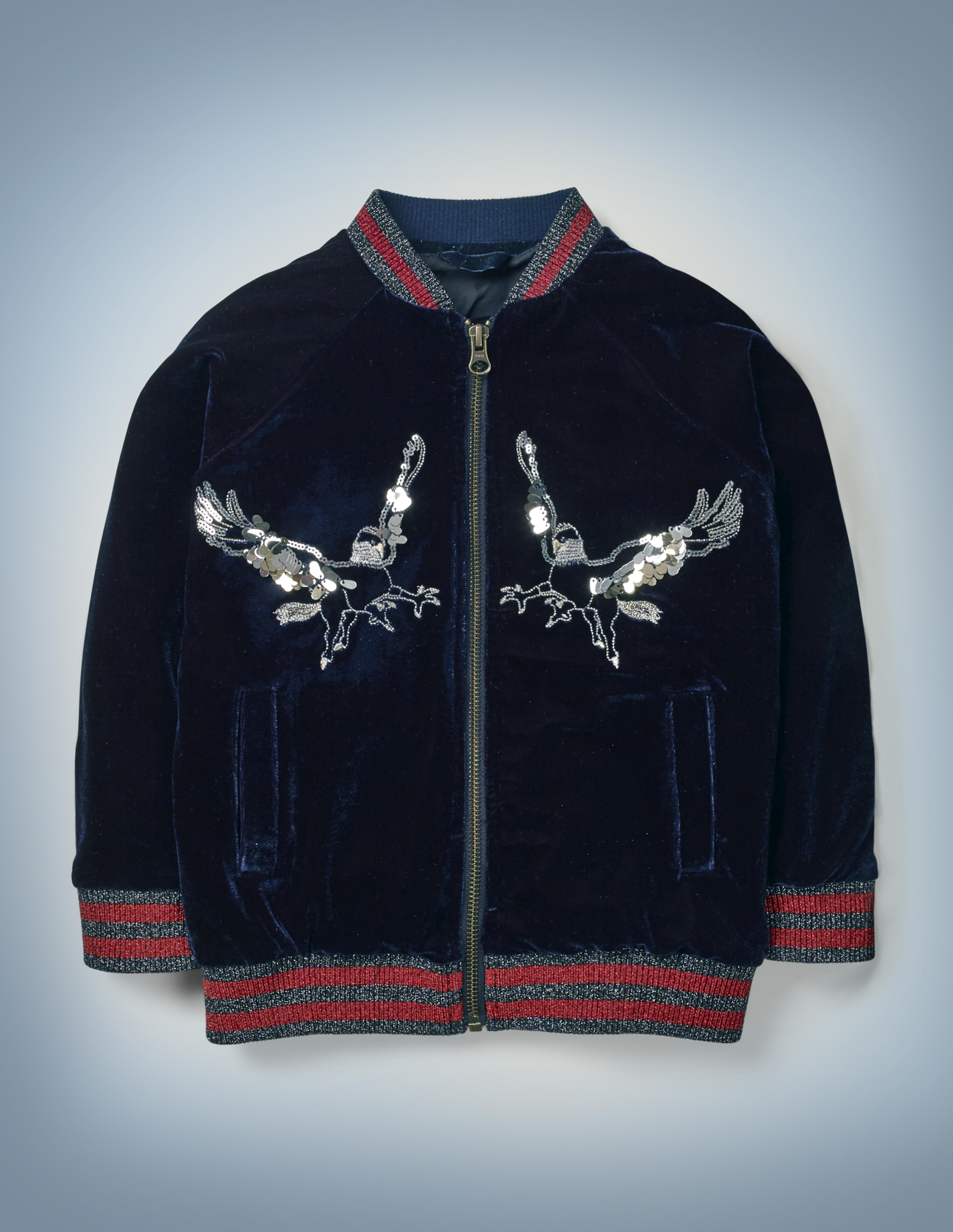 The Mini Boden Hippogriff Bomber Jacket in blue features a double-breasted, silver-sequined design of a hippogriff against the deep blue of the jacket, which features gray-and-red-striped collar and cuffs. It retails between £50 and £56.