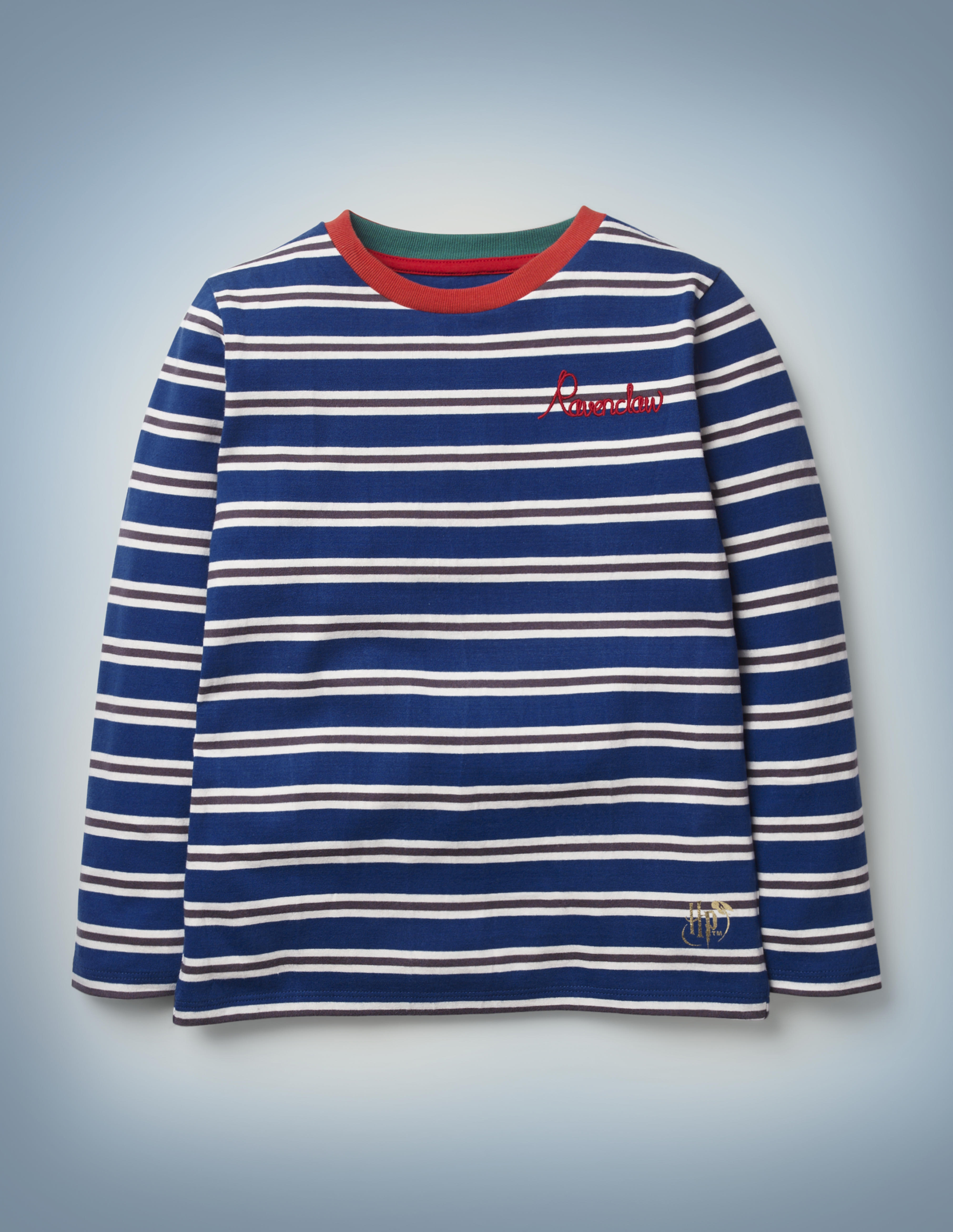 """The Mini Boden House Breton in blue features all-over blue and silver stripes, a red collar, and """"Ravenclaw"""" written in red script in the front pocket area. It retails between £20 and £22."""