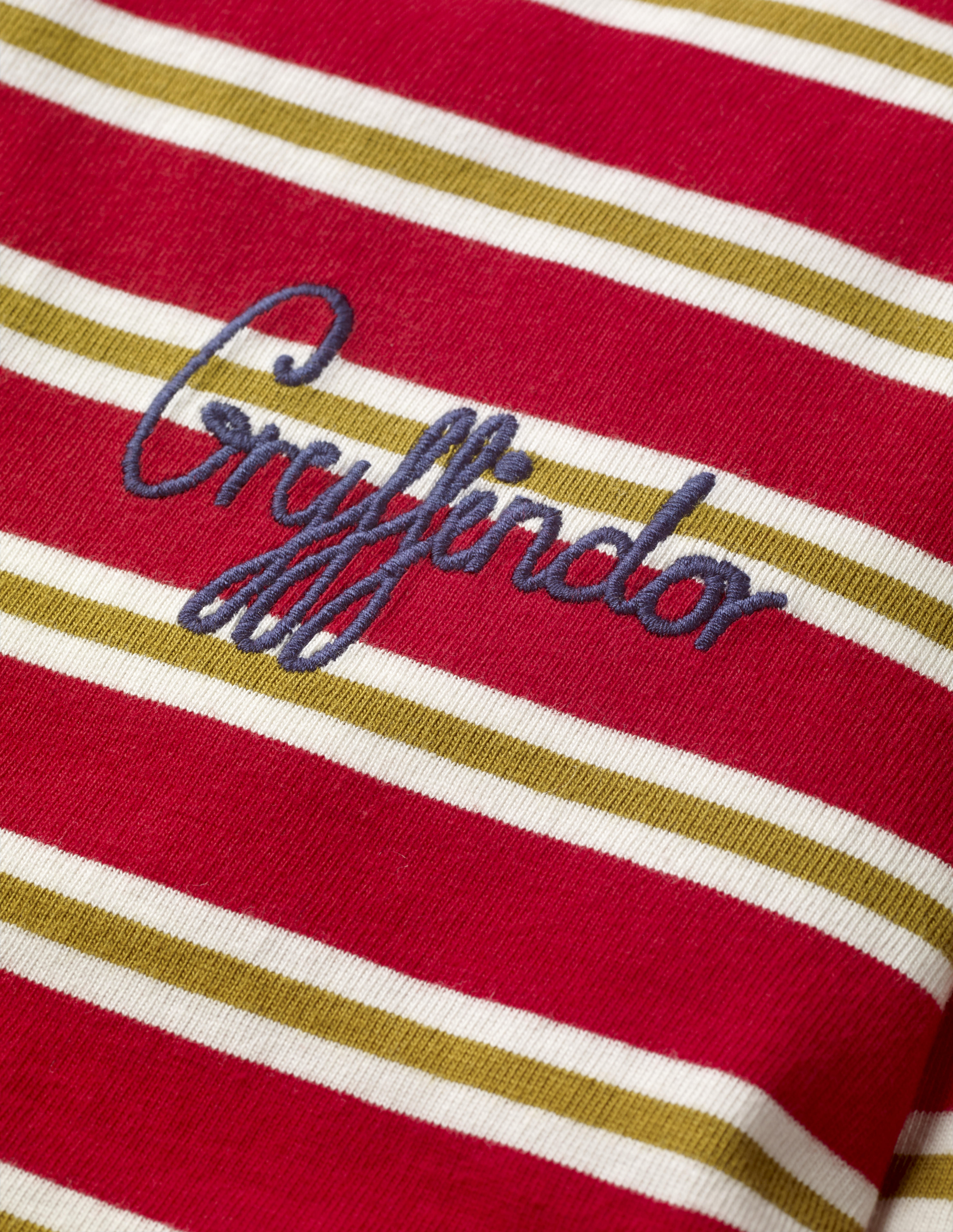 """This close-up of the Mini Boden House Breton in red better shows the word """"Gryffindor"""" written in blue script in the front pocket area. It retails between £20 and £22."""