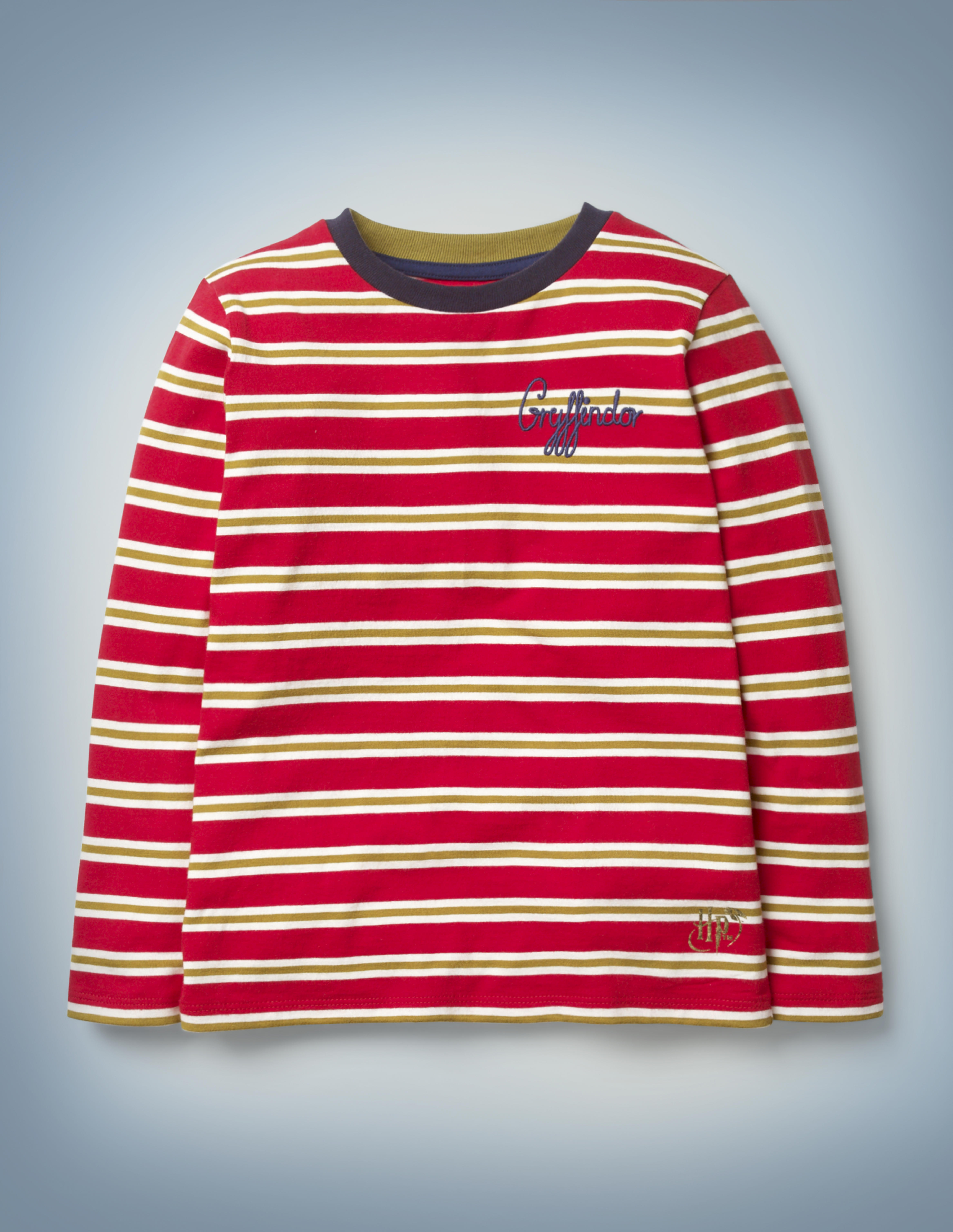 """The Mini Boden House Breton in red features all-over red and gold stripes, a blue collar, and """"Gryffindor"""" written in blue script in the front pocket area. It retails between £20 and £22."""