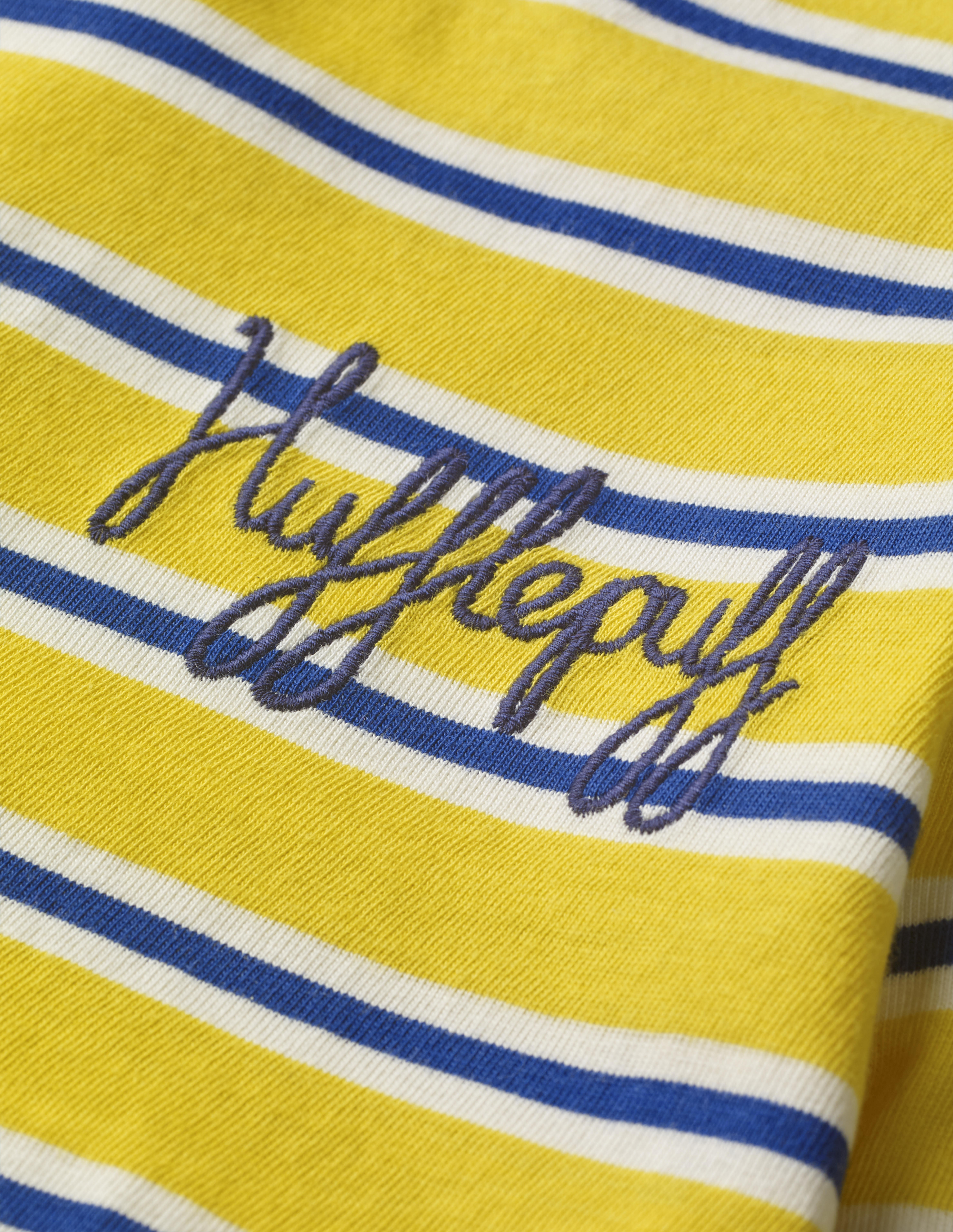 """This close-up of the Mini Boden House Breton in yellow better shows the word """"Hufflepuff"""" written in navy blue script in the front pocket area. It retails between £20 and £22."""