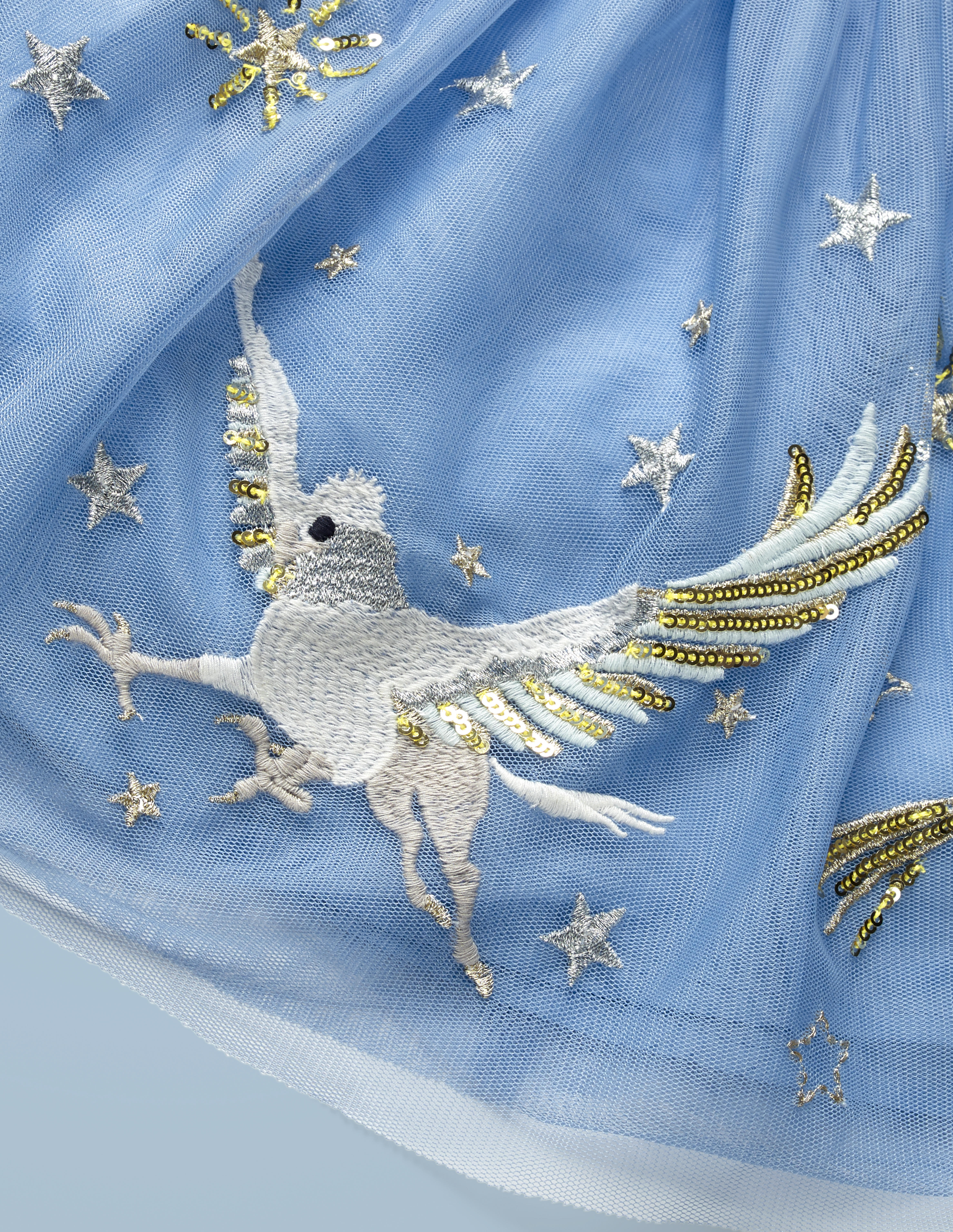 This close-up of the Mini Boden Hippogriff Tulle Skirt in light blue provides a better look at the design: a hippogriff flying among the stars. It retails at £40.