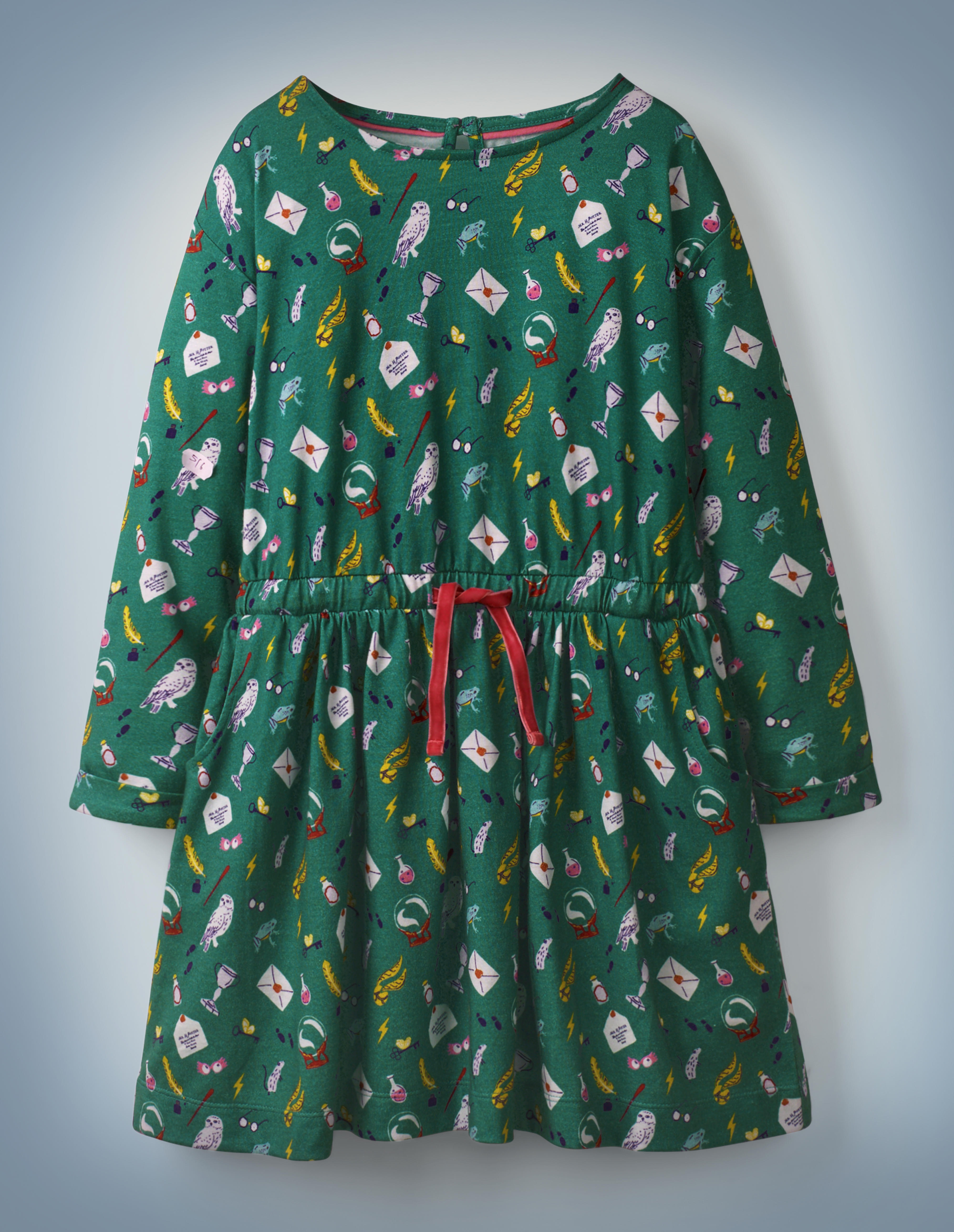 """The Mini Boden Hogwarts Printed Dress in green features an all-over pattern of iconic """"Harry Potter"""" images, including Luna Lovegood's Spectrespecs, Hedwig, and a Hogwarts acceptance letter. The dress features a red drawstring in its center. It retails at £24."""