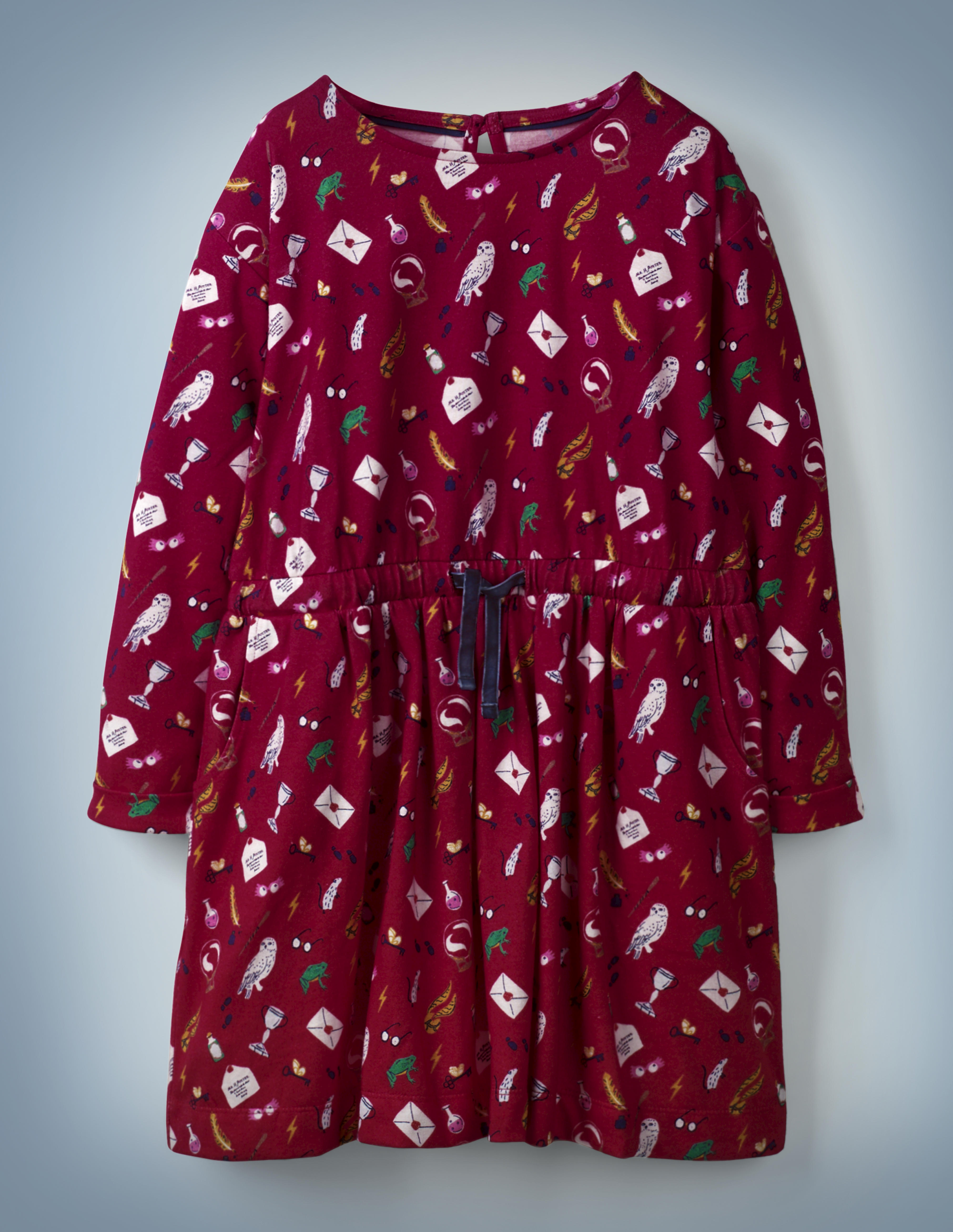 """The Mini Boden Hogwarts Printed Dress in red features an all-over pattern of iconic """"Harry Potter"""" images, including Luna Lovegood's Spectrespecs, Hedwig, and a Hogwarts acceptance letter. The dress features a navy blue drawstring in its center. It retails at £24."""