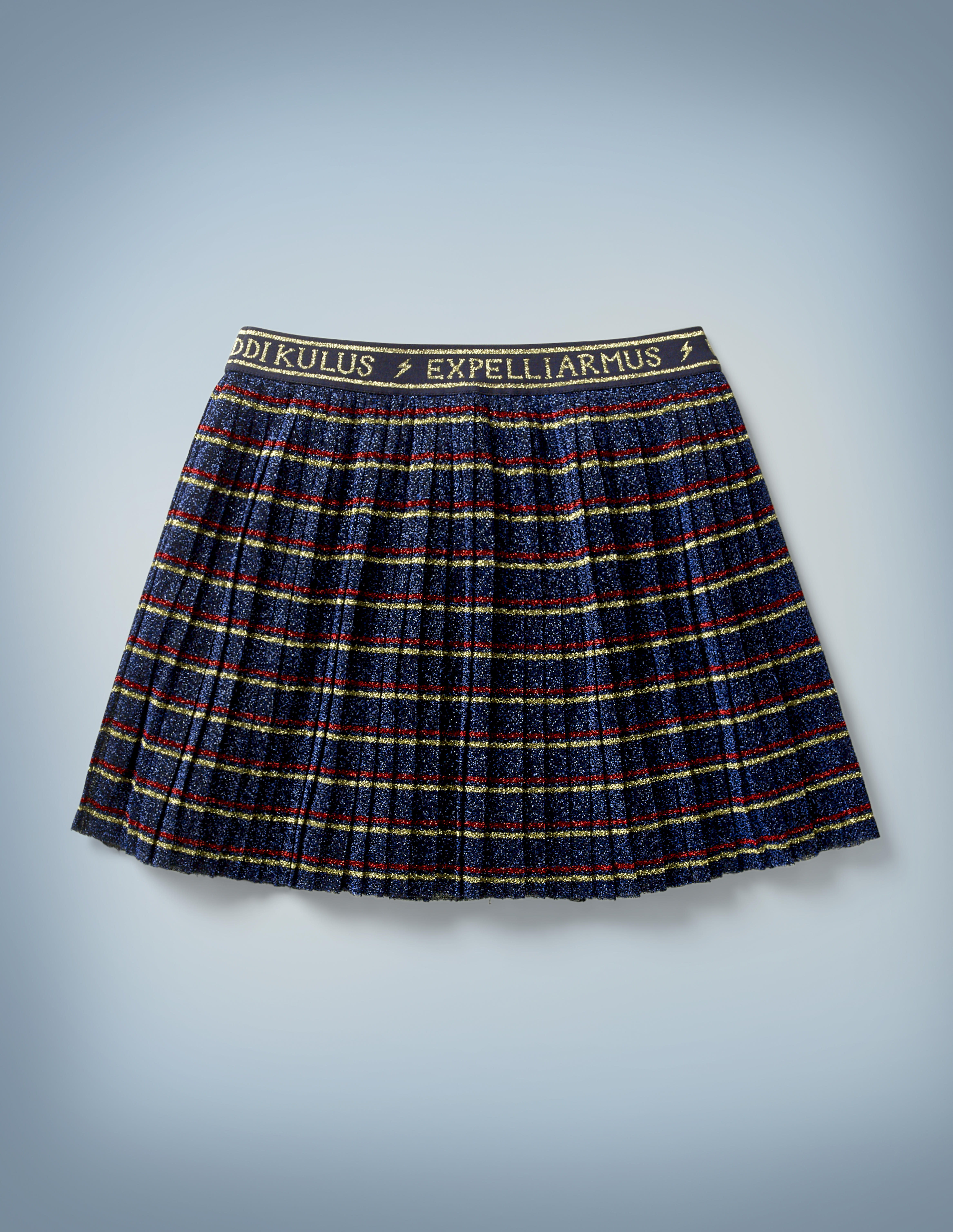"""The Mini Boden Spell Skirt is navy blue with red-and-gold stripes and a waistband that features spell incantations such as """"Riddikulus"""" and """"Expelliarmus"""" written in gold and separated by lightning bolts. It retails at £30."""