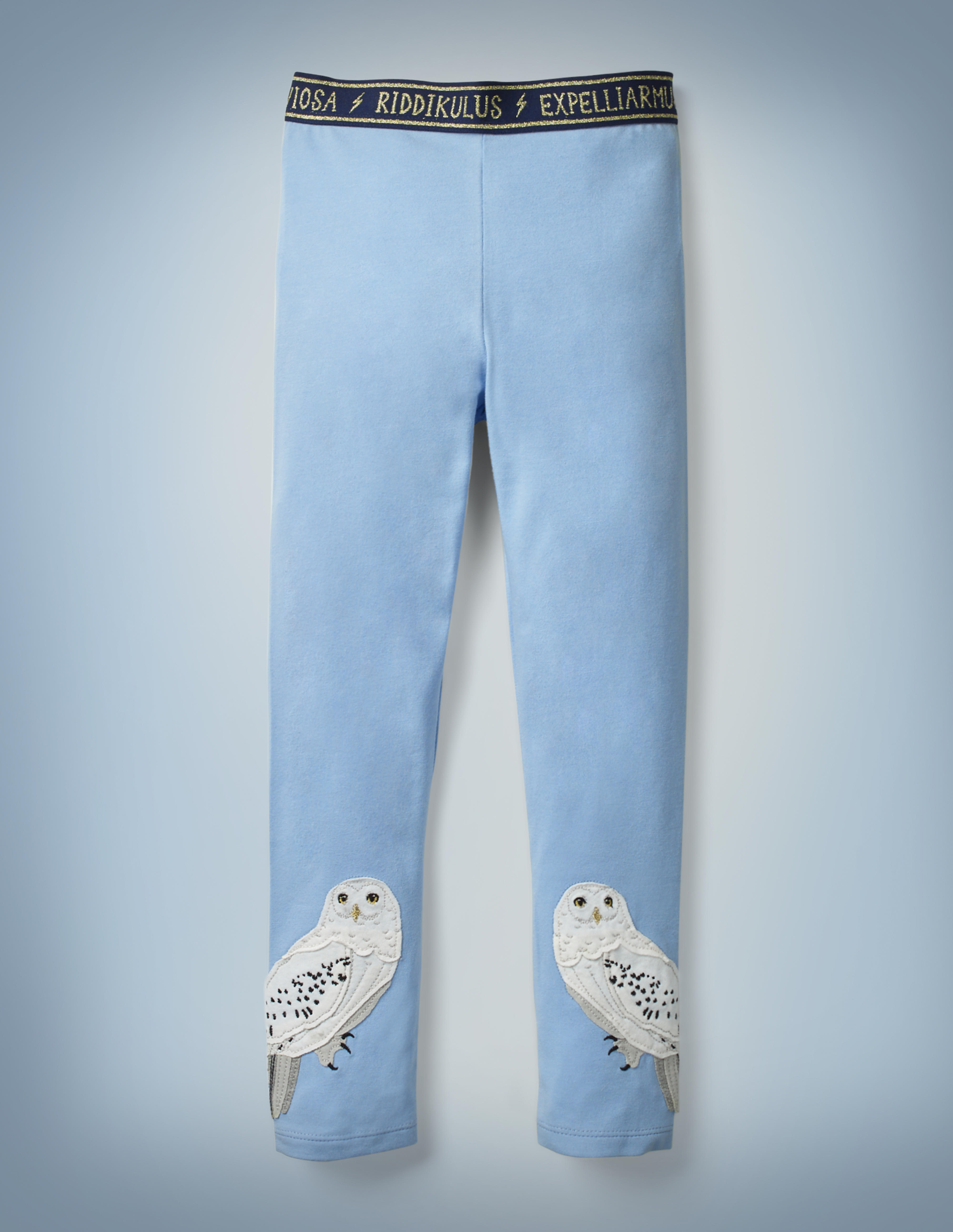 """The Mini Boden Hedwig Appliqué Leggings in light blue feature appliqué designs of Hedwig near both cuffs and a navy waistband that features spell incantations such as """"Riddikulus"""" and """"Expelliarmus"""" in gold, separated by lightning bolts. They retail for £18."""