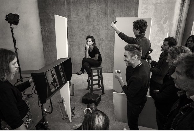 Emma Watson sits on a stool and is surrounded by lights and people during the Pirelli Calendar 2020 photoshoot.