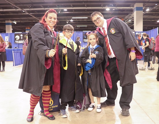 A family of four represents three Hogwarts houses wearing robes and waving wands.