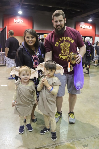 A family of four huddles together with the two children wearing house elf ears and potato sacks, and their mother wearing a Ravenclaw robe.