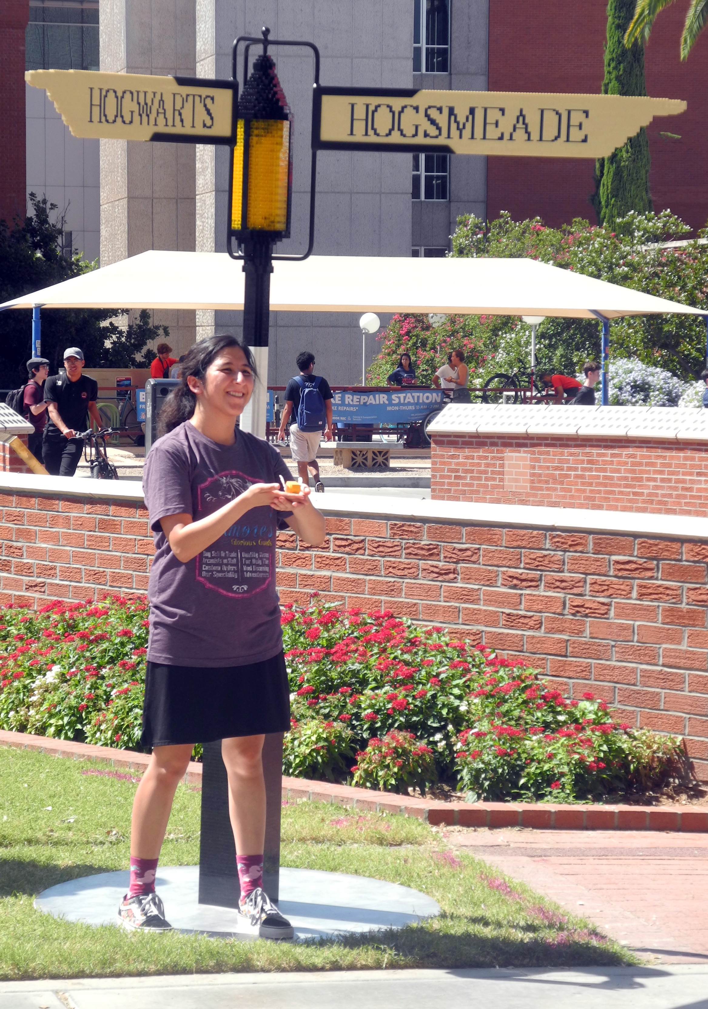 A University of Arizona student shows off the LEGO Golden Snitch she created in front of the signpost at the Back to Hogwarts event.