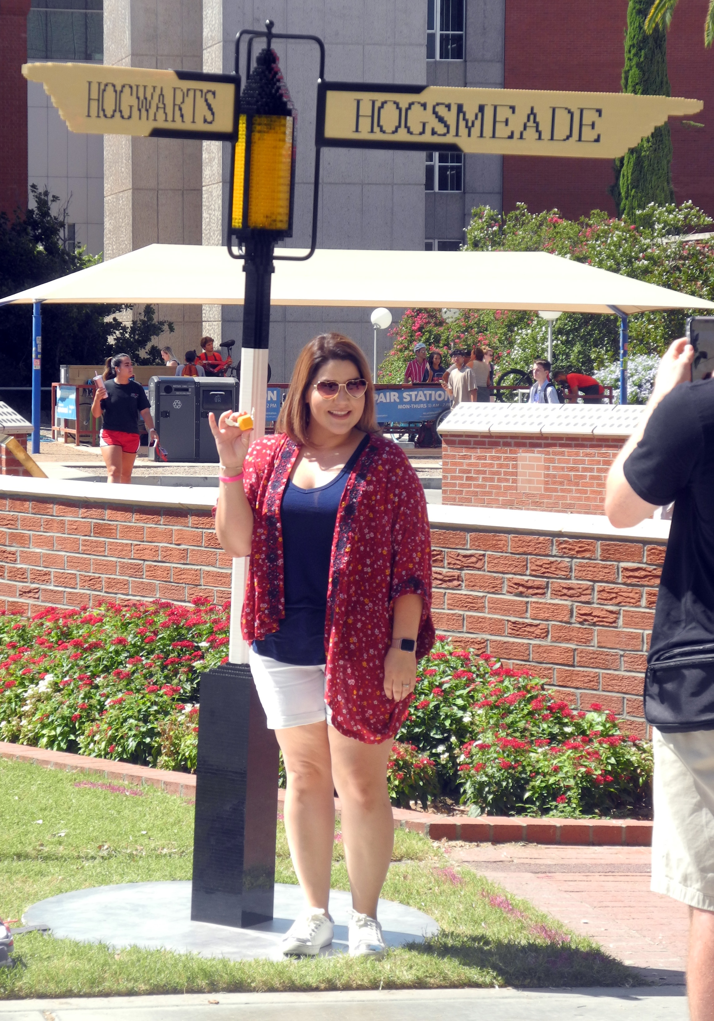 A University of Arizona student has her photo taken with the LEGO Golden Snitch she created in front of the signpost at the Back to Hogwarts event.