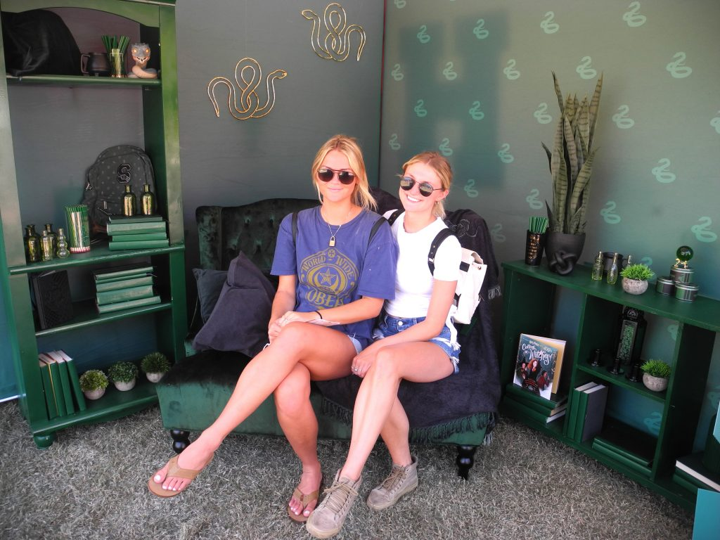 Two University of Arizona students pose in a miniature Slytherin common room during a Back to Hogwarts event at the school.