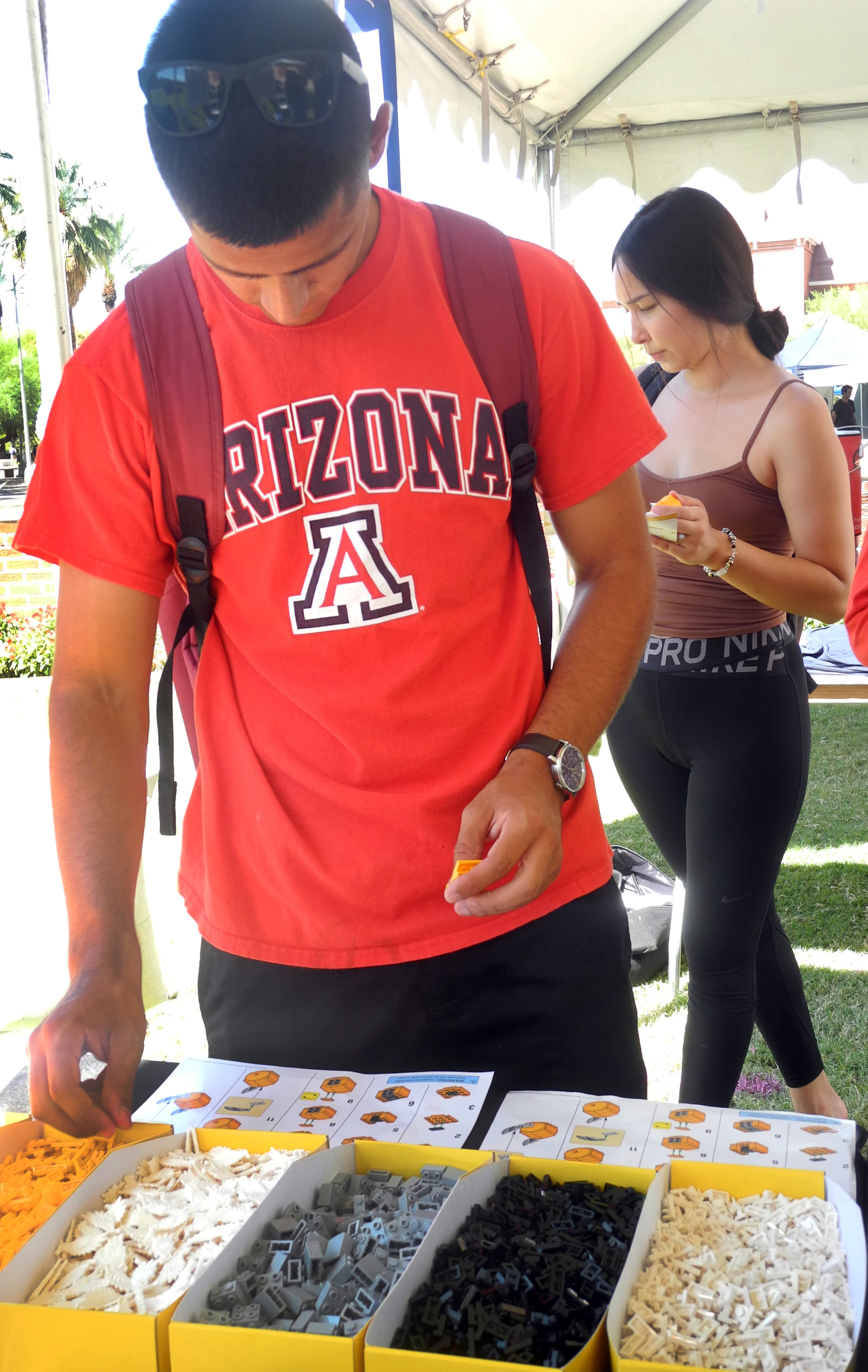 A University of Arizona student works to build a Golden Snitch from LEGO bricks during a Back to Hogwarts event at the school.