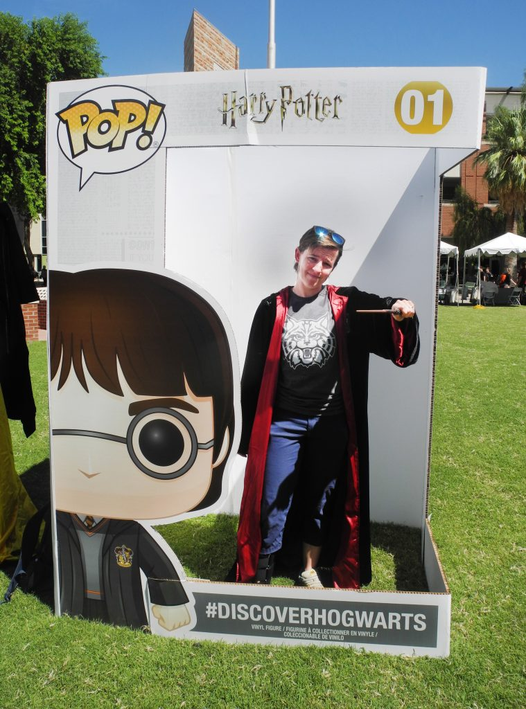 A University of Arizona student poses with a Gryffindor robe and wand in a life-sized Funko Pop! box during a Back to Hogwarts event at the school.
