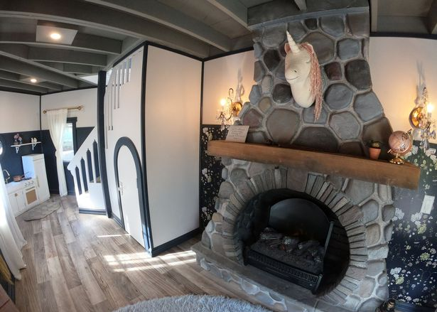 The fireplace and the cupboard under the stairs