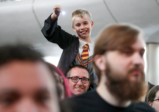 A boy waves his lighted wand over the crowd at King's Cross on Back to Hogwarts Day.