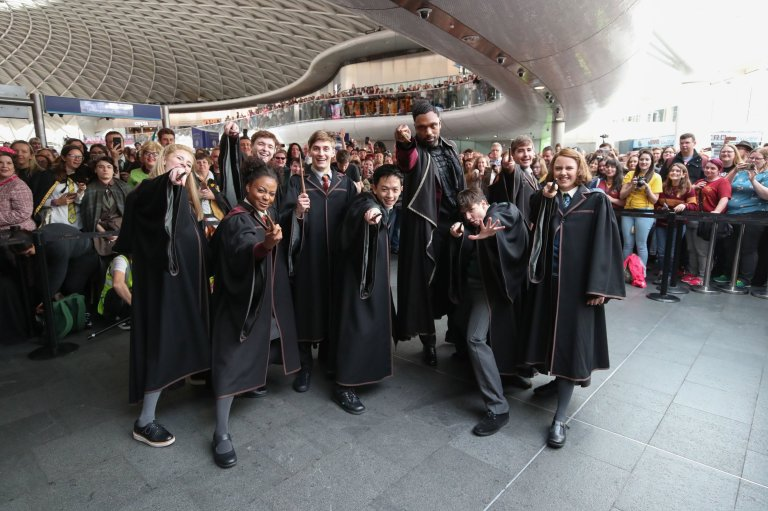 """Cast members from the West End production of """"Harry Potter and the Cursed Child"""" pose for a photo on Back to Hogwarts Day at King's Cross."""