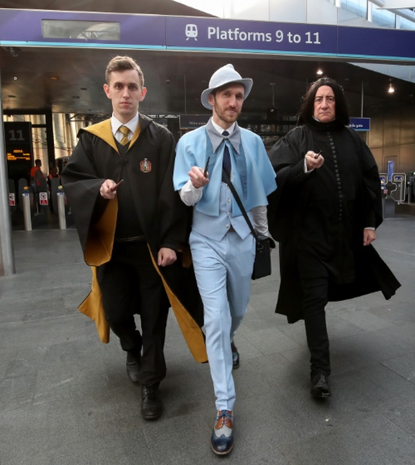 """A trio of cast members from the West End production of """"Harry Potter and the Cursed Child"""" pose for a photo on Back to Hogwarts Day at King's Cross."""