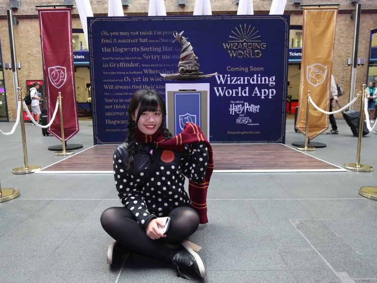 A fan poses with a new interpretation of the Sorting Hat at King's Cross.