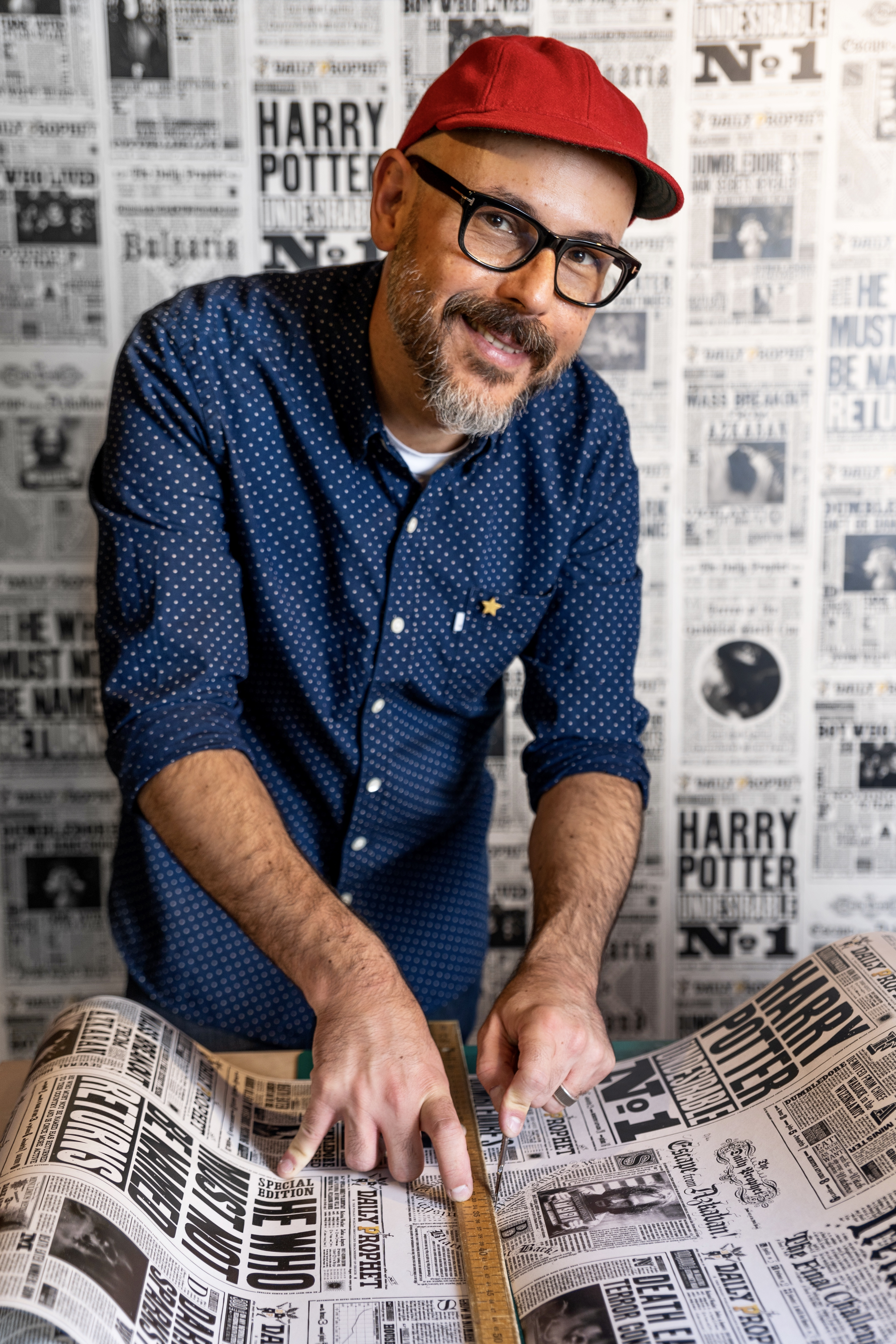 """Eduardo Lima works on MinaLima's """"Daily Prophet"""" wallpaper."""