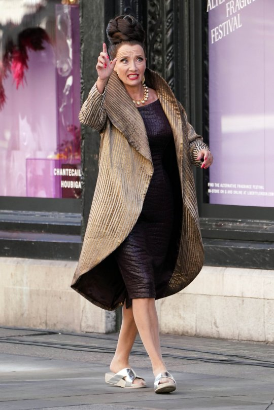 """Dame Emma Thompson looks to be hailing a car during filming for """"Cruella"""" last week in London."""