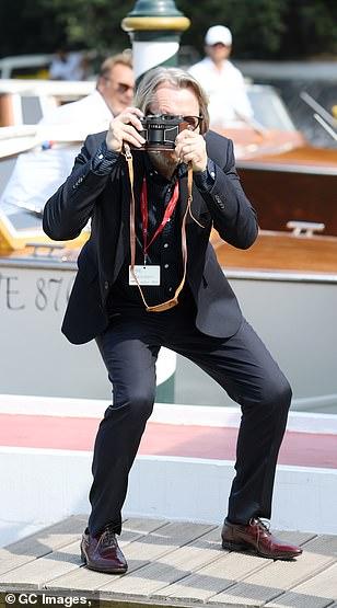 Gary Oldman jokes around with the paparazzi at the Venice International Film Festival.
