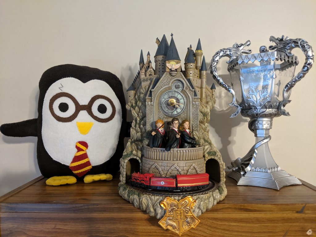 The Hogwarts wall clock next to a Harry Potter penguin and a Triwizard Cup