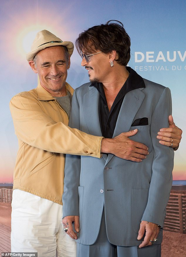 Johnny Depp smiles as he's embraced by Sir Mark Rylance at the Deauville American Film Festival in France.