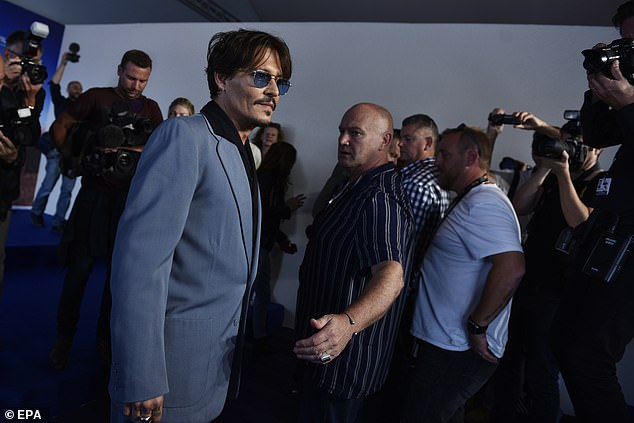 Johnny Depp makes his way through the media at the Deauville American Film Festival in France.