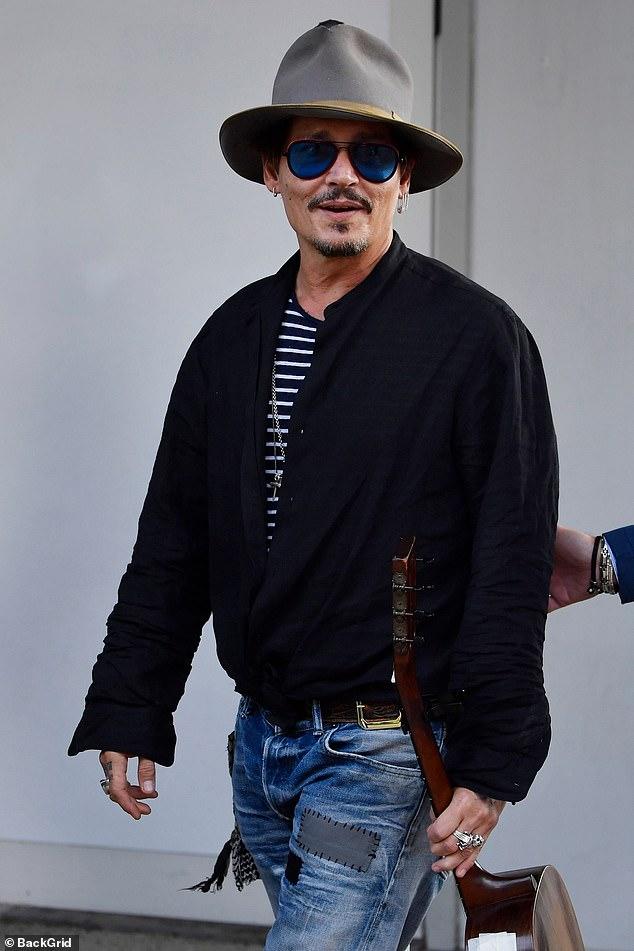Johnny Depp smiles as he arrives at the Venice International Film Festival.