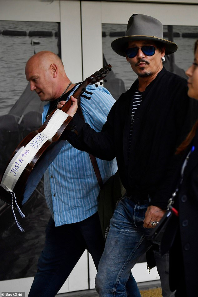 """Johnny Depp shows off his guitar, which bears masking tape reading """"Just a tad broken,"""" at the Venice International Film Festival."""