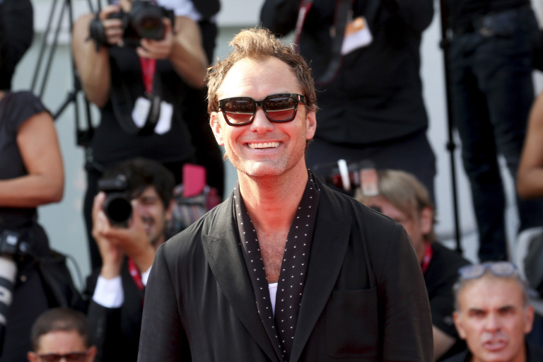 Jude Law flashes a grin on the red carpet at the Venice International Film Festival.