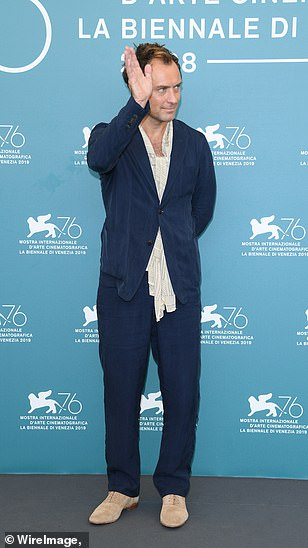 """Jude Law waves during a photo call for """"The New Pope"""" at the Venice International Film Festival."""