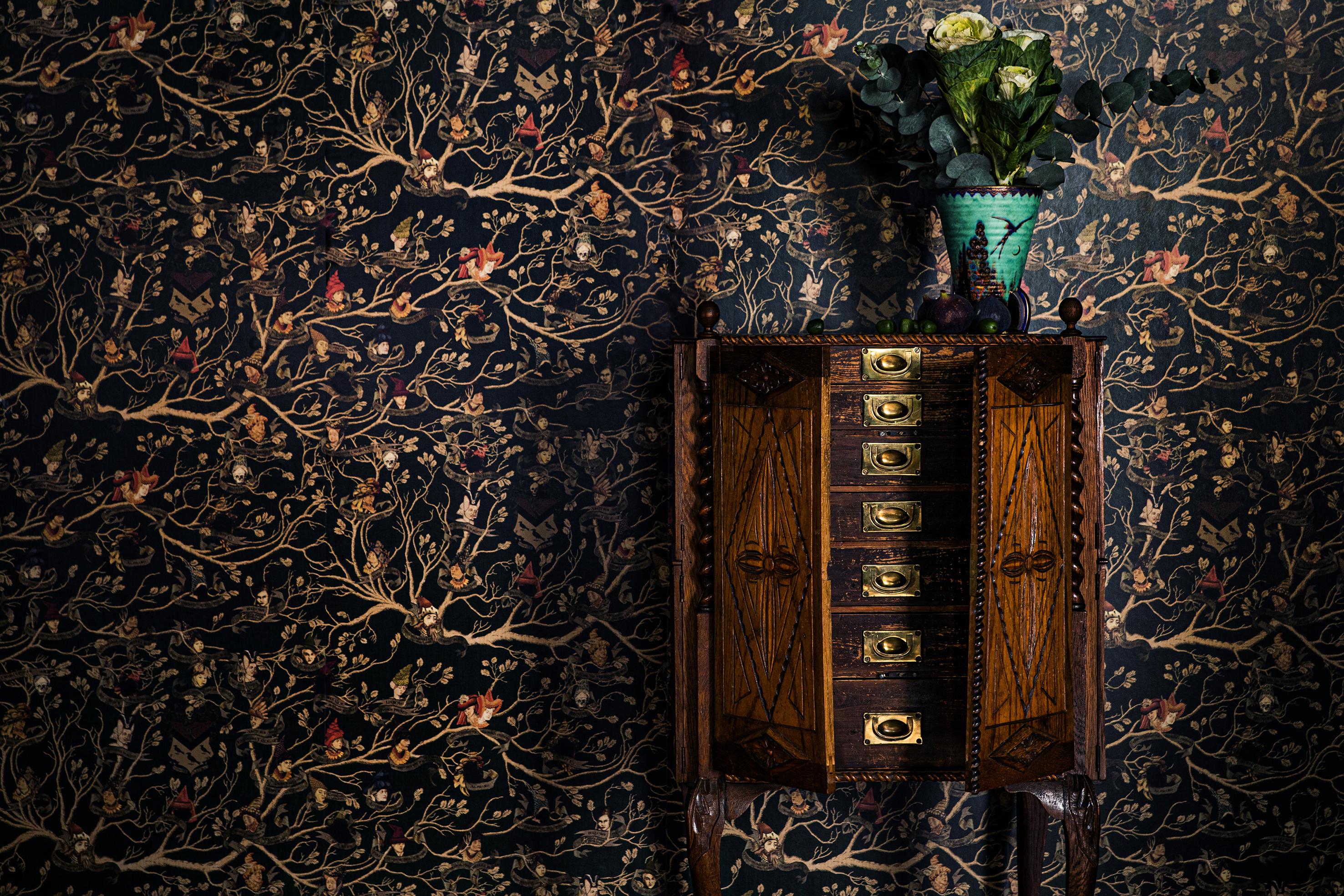The Black family tapestry wallpaper shows flourishes of branches and leaves with small portraits of the Black family members.
