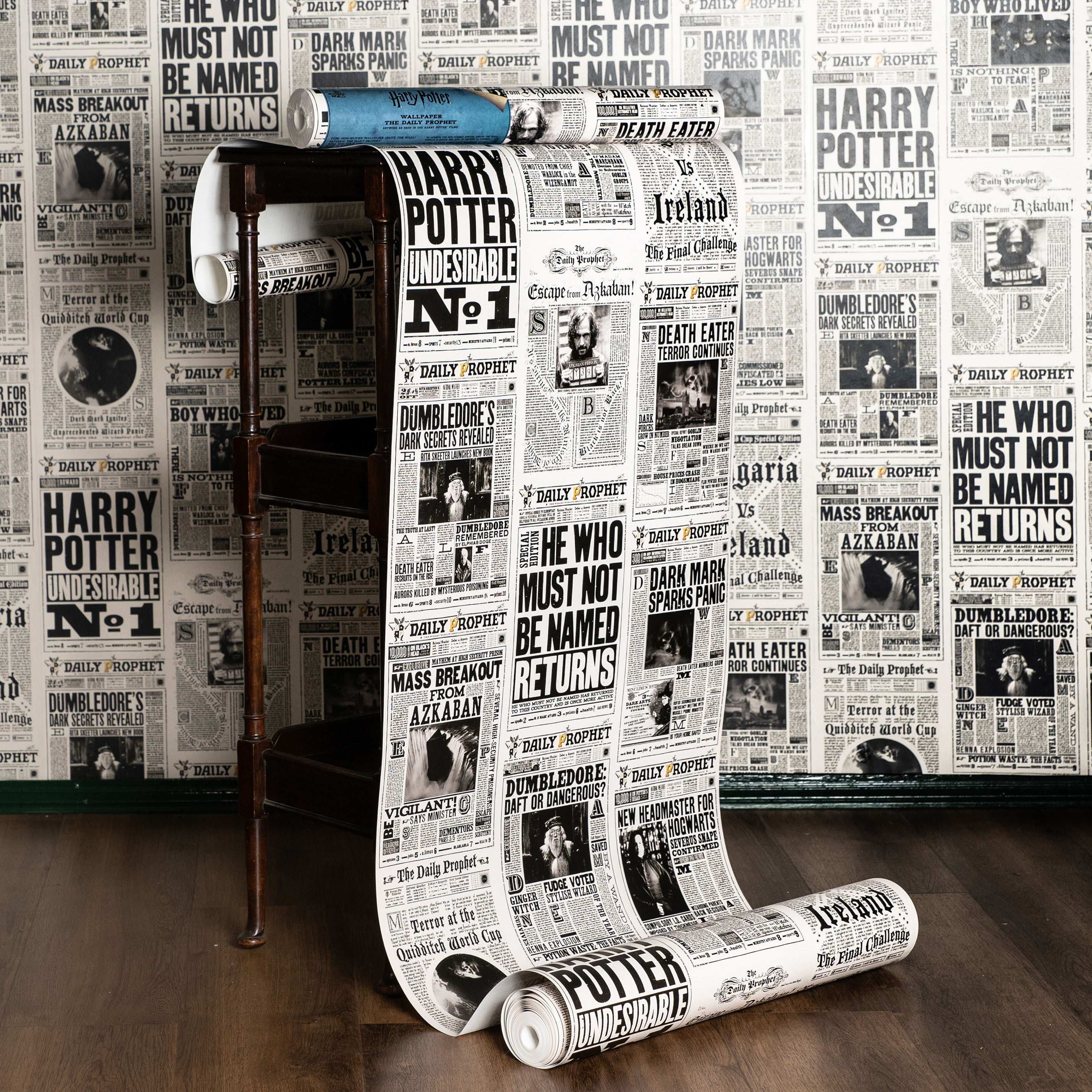 """A roll of MinaLima's """"Daily Prophet"""" wallpaper features headlines and photos from various """"Harry Potter"""" films."""