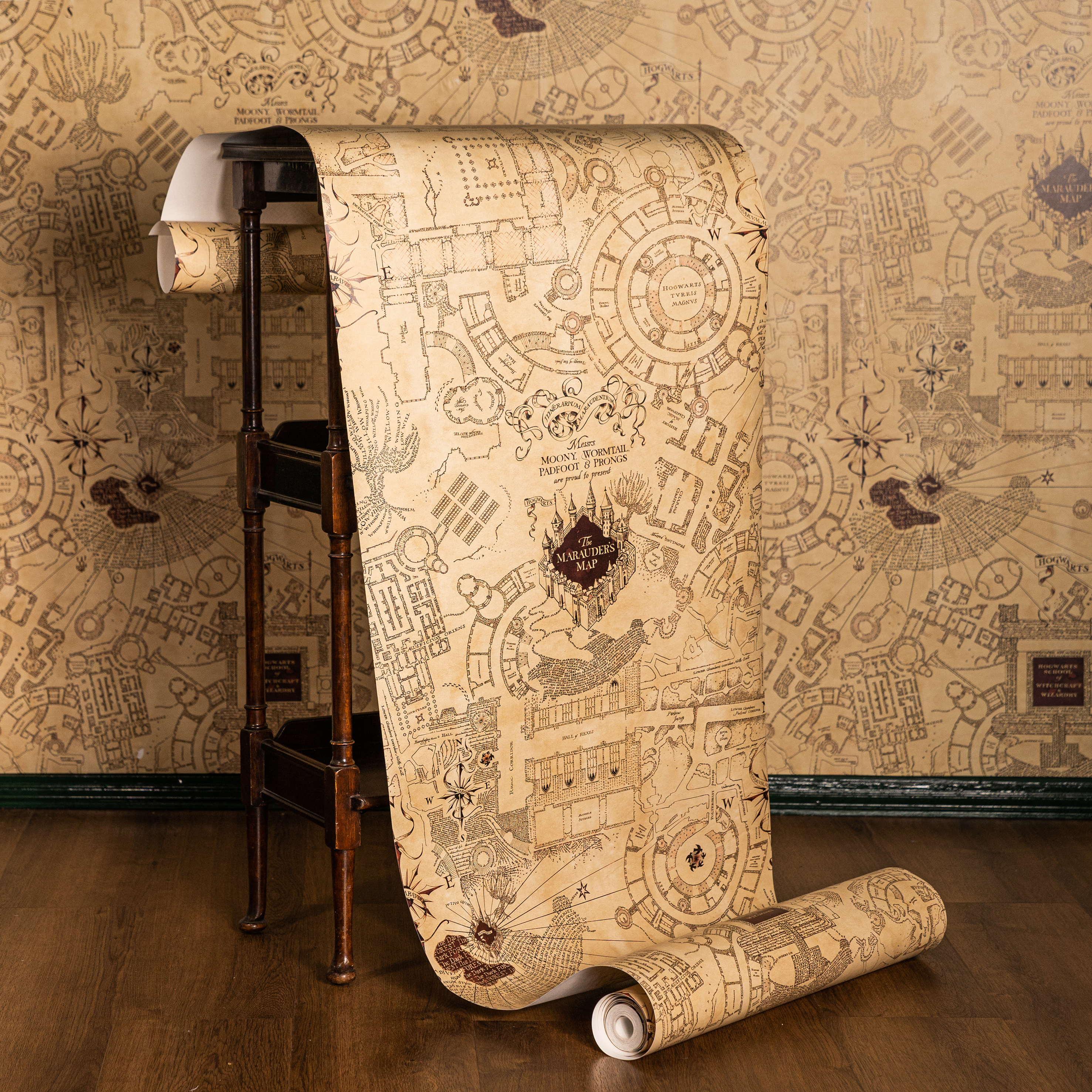 A roll of MinaLima's Marauder's Map wallpaper features the layout of Hogwarts Castle.