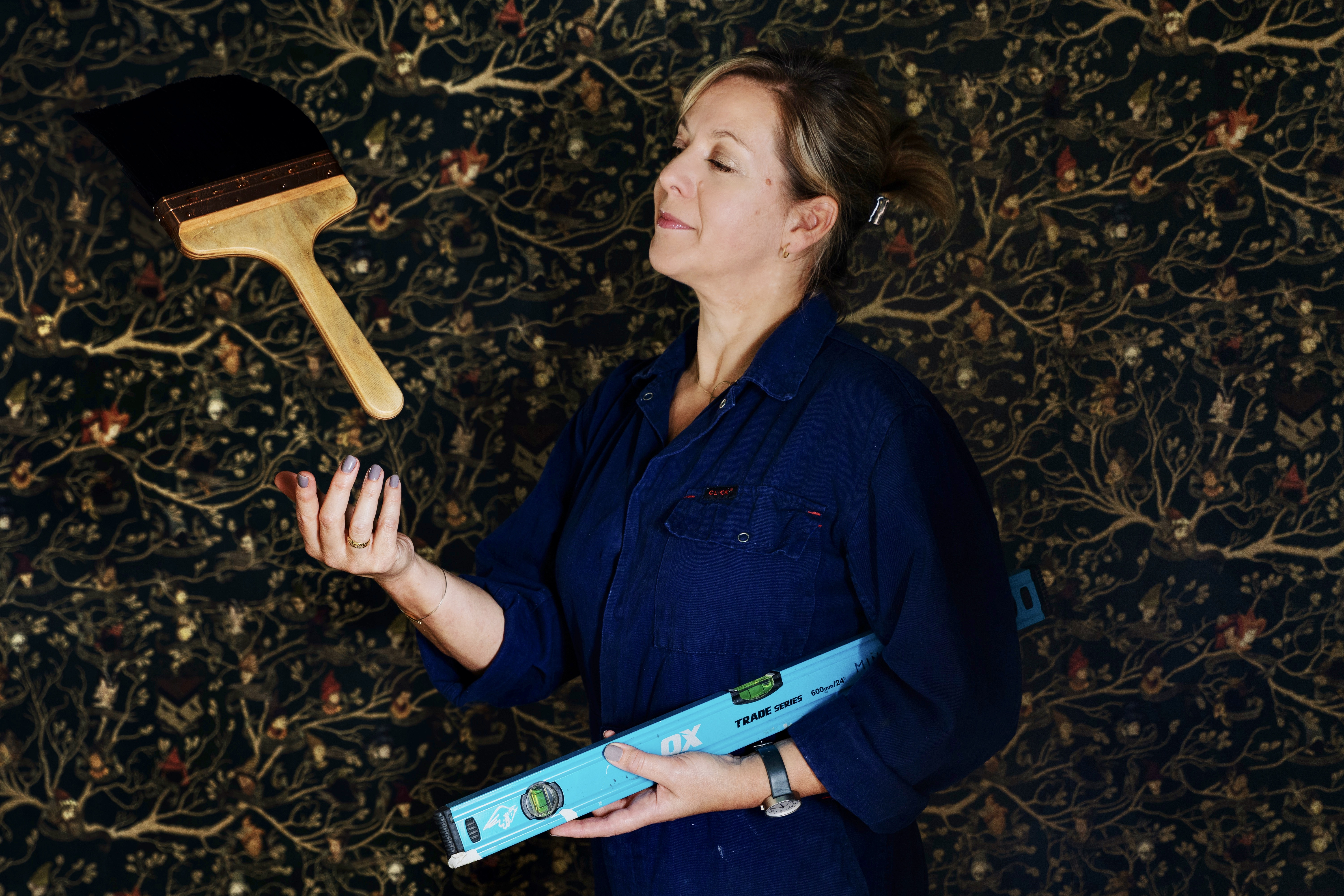 Designer Miraphora Mina, with a paste brush and leveler in hand, looks ready to apply wallpaper to any and every surface!