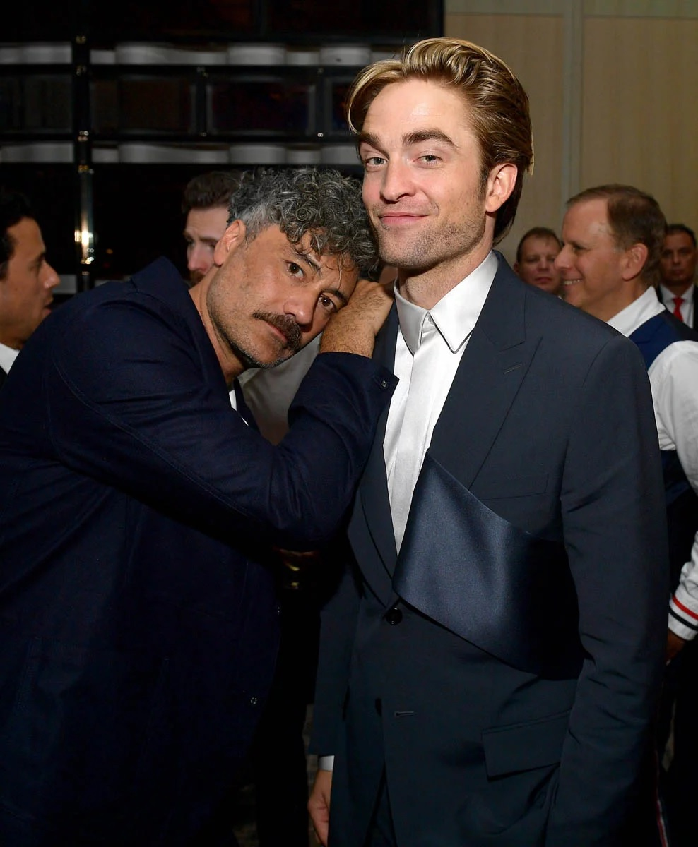 Robert Pattinson shares a tender moment with Taika Waititi at the Toronto International Film Festival.