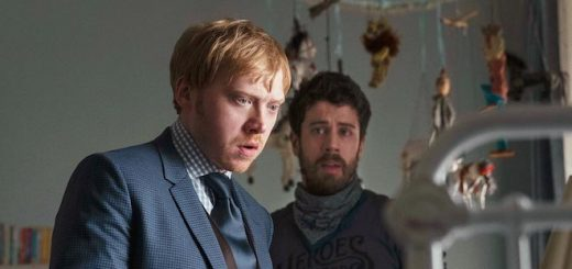 "Rupert Grint and Toby Kebbell stare into a baby's crib in a still from the upcoming Apple TV+ series, ""Servant""."