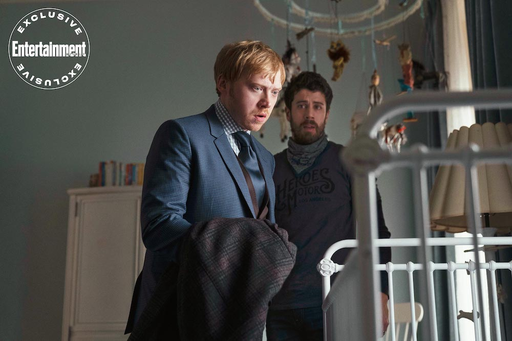 """Rupert Grint and Toby Kebbell stare into a baby's crib in a still from the upcoming Apple TV+ series, """"Servant""""."""