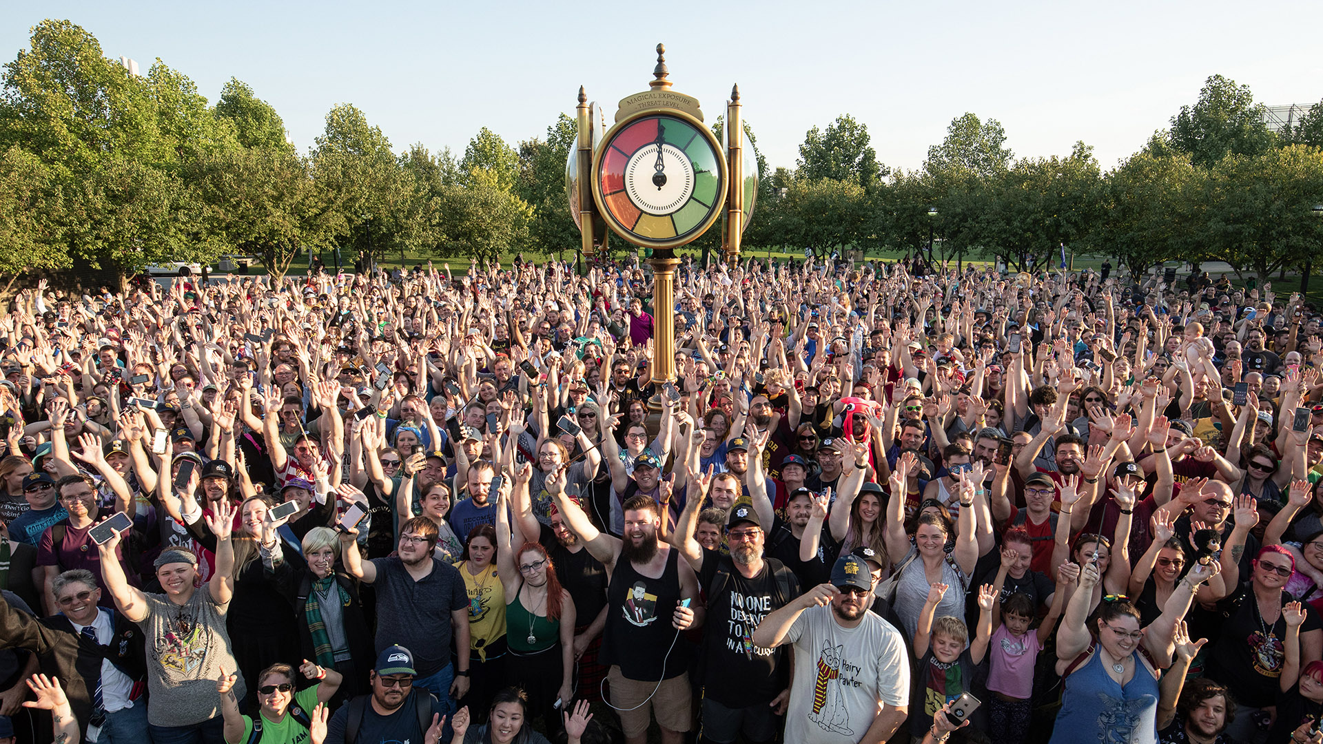 """Attendees of the """"Harry Potter: Wizards Unite"""" Fan Festival pose for a group photo around the life-sized Threat Clock."""