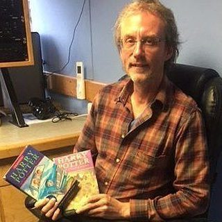 Illustrator Cliff Wright proudly holds two Harry Potter books