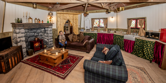 A woman sits inside a Hagrid's Hut replica, surrounded by beams, couches, and a fireplace.