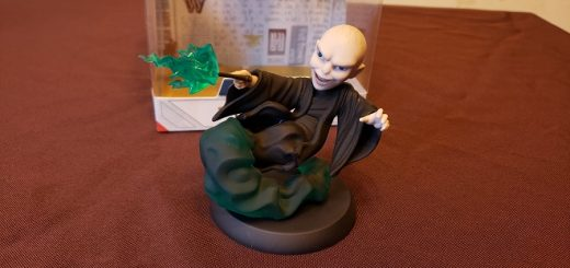 Image of a vinyl figure of Voldemort, his wand at the ready, with green smoke below him and green sparks shooting from his wand.