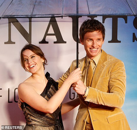 "Eddie Redmayne laughs on the red carpet with ""The Aeronauts"" costar Felicity Jones at the London Film Festival."