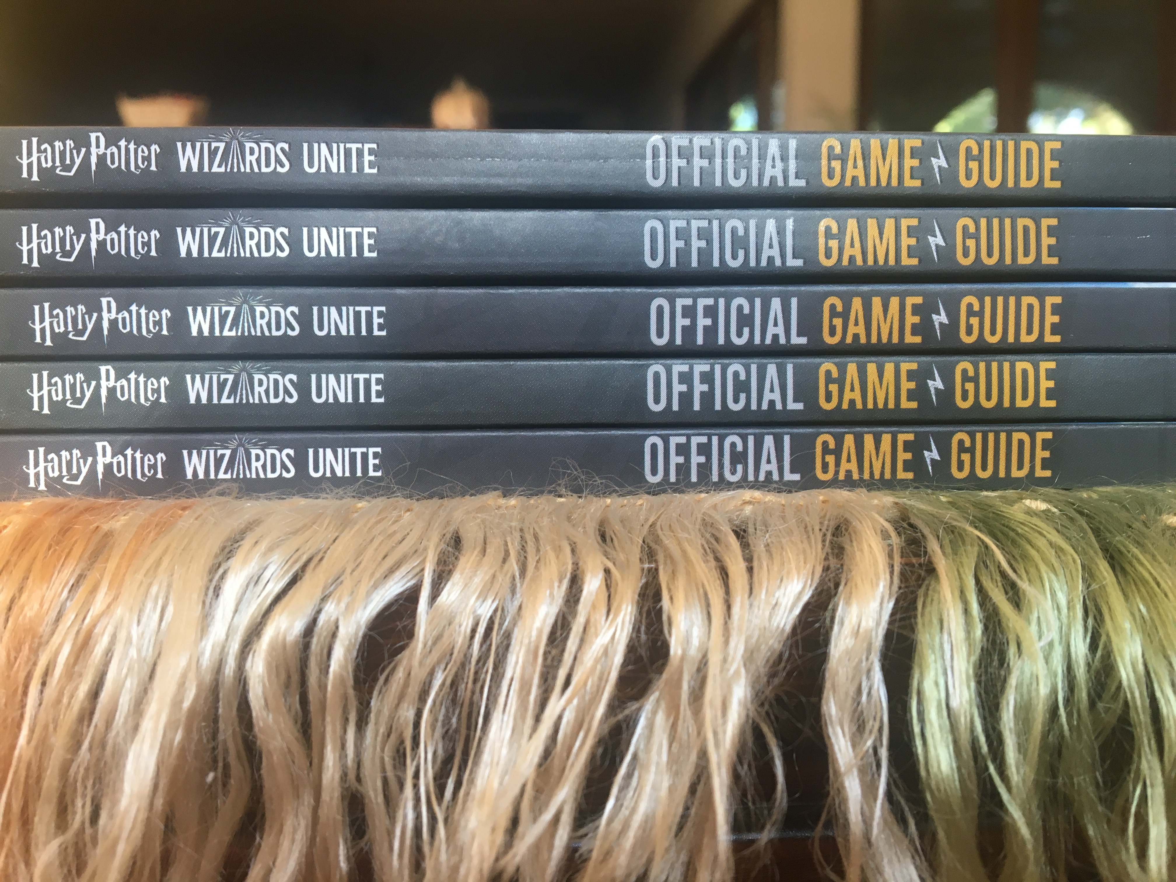 """Harry Potter: Wizards Unite: Official Game Guide"", stack of books"