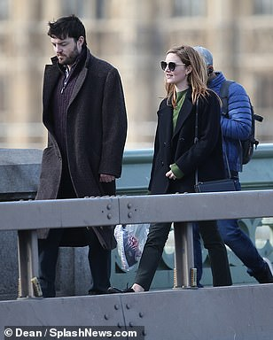 "Holliday Grainger as Robin Ellacott and Tom Burke as Cormoran Strike walk along a bridge during filming for ""Lethal White"" in London."
