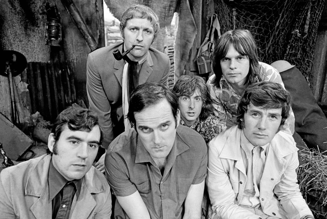 "Terry Jones, Graham Chapman, John Cleese, Eric Idle, Terry Gilliam, and Michael Palin are pictured on the set of ""Monty Python's Flying Circus""."